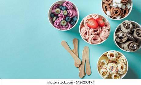 rolled ice creams in cone cups on blue background. Different iced rolls top view or flat lay. Thai style rolled ice cream with copy space for text or design. Banner