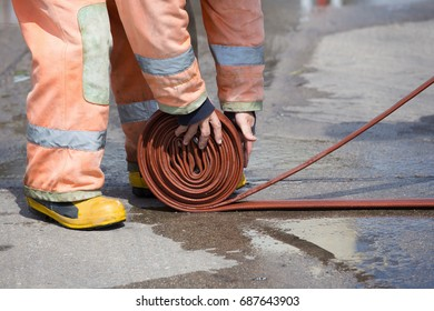 Rolled into a roll red fire hose, Fire equipment extinguishers ready to use in the outdoor.