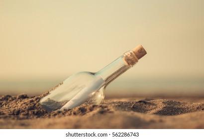 Rolled letter inside glass bottle on a beach