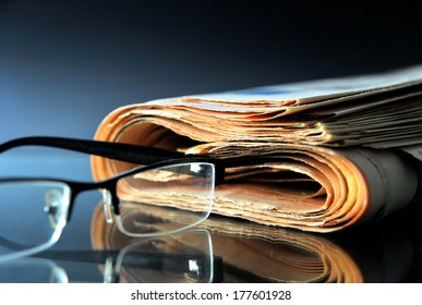 Rolled up newspaper with glasses