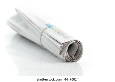 Rolled up newspaper with rubber band on white background