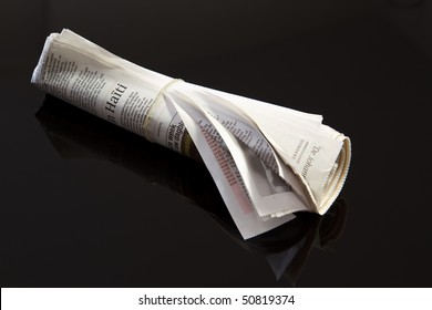 rolled up newspaper with rubber band on black