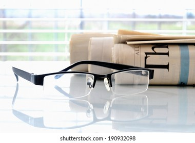 Rolled newspapers with glasses in front of a window