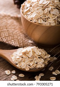 Rolled oat flakes in a wooden spoon and bowl.
