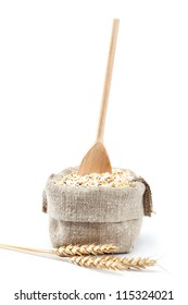 Rolled oats in a bag with a wooden spoon and wheat ears isolated on white background.