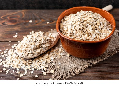 Rolled oats in bowl on dark wooden background.
