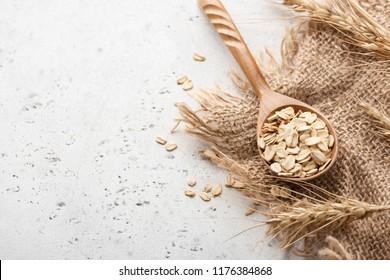 Rolled oats and ears of wheat on concrete background with copy space for text