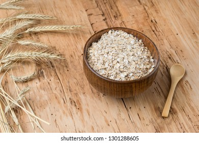 Rolled oats or oat flakes in bowl with wooden spoons, golden wheat ears rustic wooden background. Healthy lifestyle, healthy eating concept