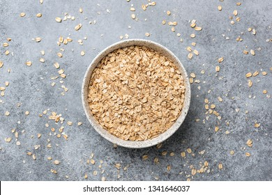 Rolled oats or oat flakes in bowl, table top view. Concept of healthy eating, dieting, vegan or vegetarian diet