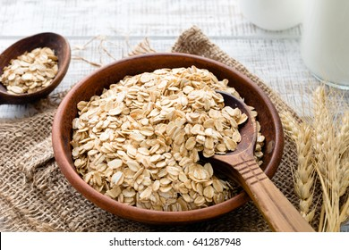 Rolled oats or oat flakes in bowl with wooden spoons, golden wheat ears and bottle of milk on background. Healthy lifestyle, healthy eating concept