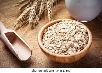 Rolled oats (oat flakes), milk and golden wheat ears on wooden background. Raw food ingredients, healthy lifestyle, cooking food