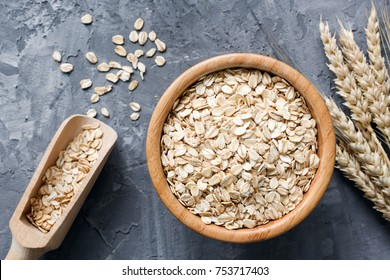 Rolled oats or oat flakes in wooden bowl and golden wheat ears on stone background. Top view, horizontal. Healthy lifestyle, healthy eating, vegan food concept