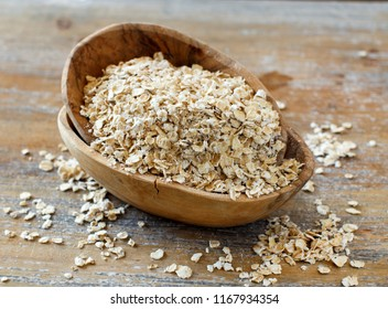Rolled oats in a wooden bowl close up