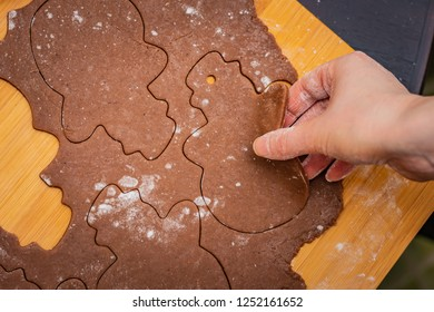 Rolled out dough on a table top with cut-out snowmen, preparation for Christmas, baking gingerbread cookies, hand raising one snowman