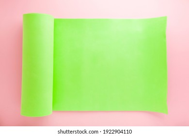 Rolled out green foam fitness mat on light pink floor background. Pastel color. Closeup. Empty place for motivational, inspirational text.
