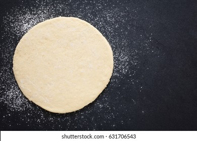 Rolled out pizza dough on floured slate surface, photographed overhead with natural light