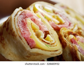 rolled pancakes stuffed ham and cheese. Shallow depth-of-field.
