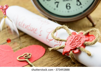 Rolled up scroll of love poem fastened with natural brown jute twine hemp rope, sealed with sealing wax and stamped with alphabet letter B. Decorated with a red mulberry paper heart and a brass key.