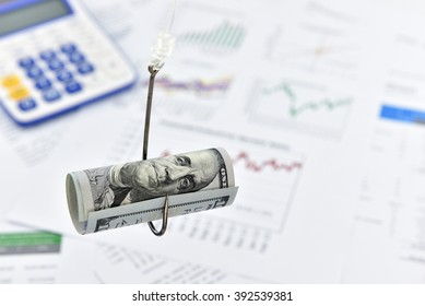 Rolled up scroll of US 100 dollar bill on a fishing hook. A concept of deceiving someone in several fields/market/trading i.e. financial, currency, forex, stock, equity, bond, derivatives, shares, etc