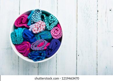rolled socks in enamel bowl, on white wood table