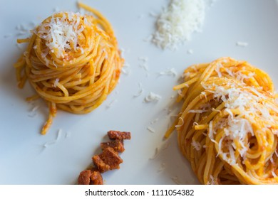 Rolled spaghetti, chorizo and tomato with grated cheese in a white dish