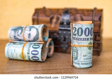 Rolled up and stacked 20000 forint banknotes with a closed vintage wooden box in the background