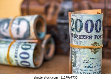 Rolled up and stacked 20000 forint banknotes with a closed vintage wooden box in the background close up