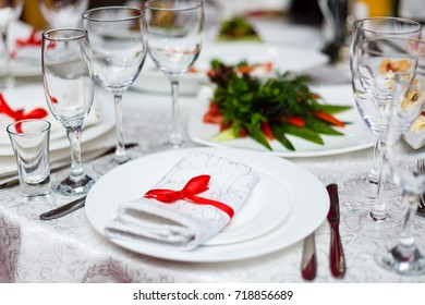 Rolled table napkin tied with red ribbon on white empty plate on table. Table setting, free space. Table served for wedding banquet, close up view