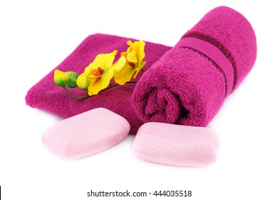 Rolled towel, flowers and soaps isolated on white background.