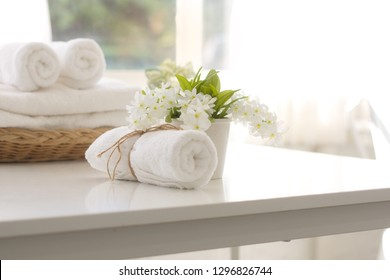 Rolled towels and flower vases placed on a white table