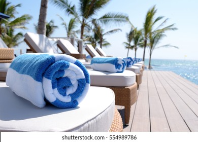 Rolled up towels on sunbeds by pool