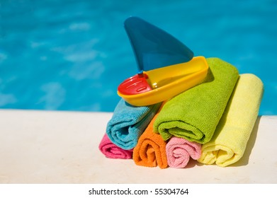 Rolled towels and plastic boat near the swimming pool