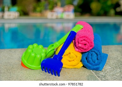Rolled towels and plastic toys at the swimming pool on vacation