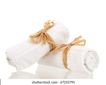Rolled up towels with reflections on pure white background