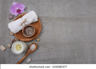 Rolled towels and salt in wooden bowl, sea salt in spoon, candles ,stone and pink orchid flowers on grey background. Spa concept. Place for text