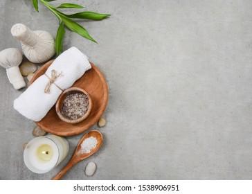 Handtücher und Salz in Holzschüssel, Bambus, Steinöl und ätherisches Öl, Kräuterball auf grauem Hintergrund. Spa-Konzept. Ort für Text