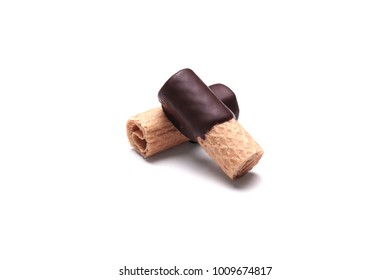rolled waffle pastry with dark chocolate coating on white background with shadow, called Waffelroellchen or small waffle rolls in Germany