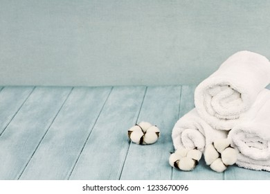 Rolled up white fluffy towels with cotton flowers against a blurred blue background with free space for text.