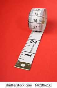 A rolled up white tape measure with both inches and centimetres on a red paper background
