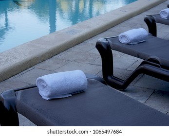 Rolled white towels placed in loungers by a swimming pool