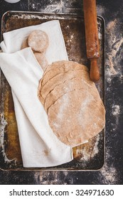 Rolled wholegrain dough with dough balls and rolling pin over on a flourish baking dirty sheet on a  dark table. Step on step preparing flatbread.