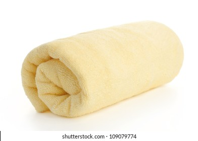 rolled up yellow beach towel on  white background