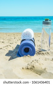 Rolled Yoga Mat Bottle with Water White Towel on Beach Sand with Turquoise Sea Blue Sky in Background. Sunlight. Relaxation Summer Meditation Fitness Wellbeing Mindful Living Concept. Copy Space