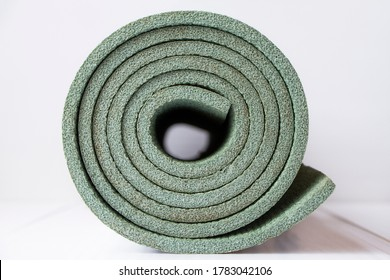 Rolled yoga mat on a white background. Travel mat made of foam. A roll of polystyrene.