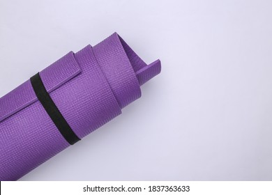 Rolled yoga mat on white background. Healthy lifestyle concept. Top view