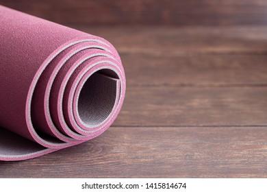 Rolled yoga mat on wooden floor, concept for start the doing Ashtanga yoga. Copy space.