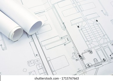 Rolled-up plans on another architectural plan of an extended apartment building