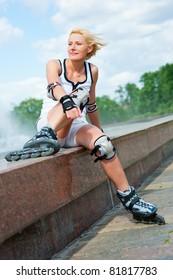 Roller blonde girl resting on the border