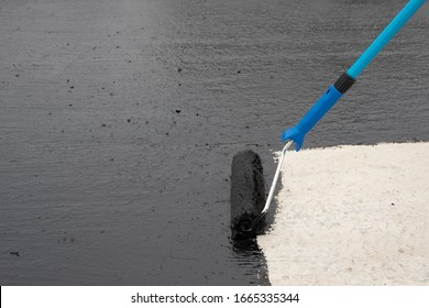 roller brush on concrete. Waterproofing coating. Copy space. Space for text.  closeup. Tools.