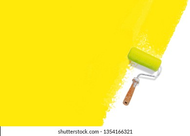 roller brush with yellow painted wall - colorful renovation concept